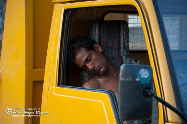 Truck driver sleeping inside truck
